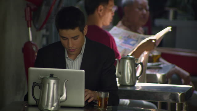 vídeos de stock, filmes e b-roll de ms young business man using laptop sitting in outdoor restaurant, bangkok, ayuthaya, thailand - traje completo