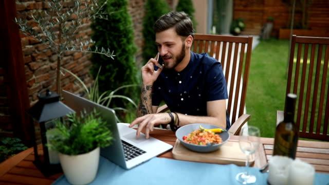 stockvideo's en b-roll-footage met jonge zakenman met behulp van de telefoon en laptop buiten - freelancer