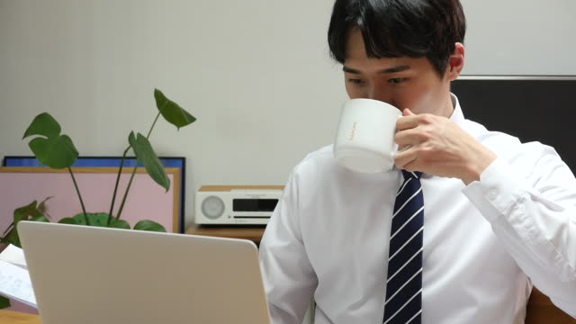 young business man working at home while drinking a cup of coffee - コーヒーカップ点の映像素材/bロール
