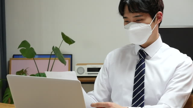 stockvideo's en b-roll-footage met young business man working at home while wearing a face mask - overhemd en stropdas
