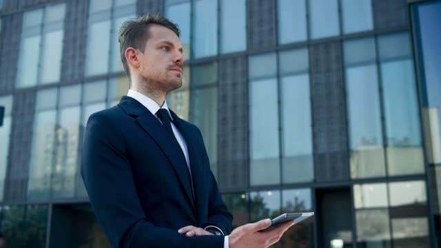 vídeos y material grabado en eventos de stock de ds joven hombre de negocios que trabaja en su tableta fuera del edificio de negocios y a alejarse - determinación