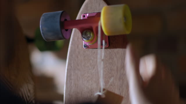 vídeos de stock, filmes e b-roll de young business owner hangs price tag around colorful skateboard wheel - sales occupation
