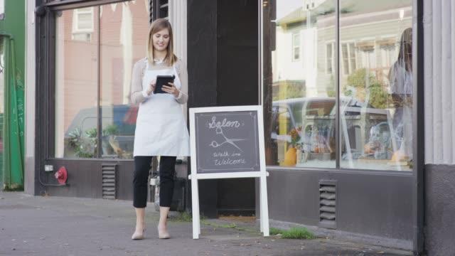 Propriétaire de l'entreprise jeune tenant un dispositif de paiement sans fil
