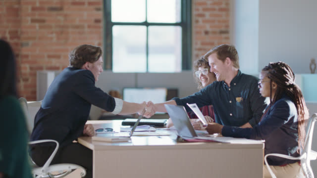 young business partners come to agreement, smile as they shake hands - collega d'ufficio video stock e b–roll