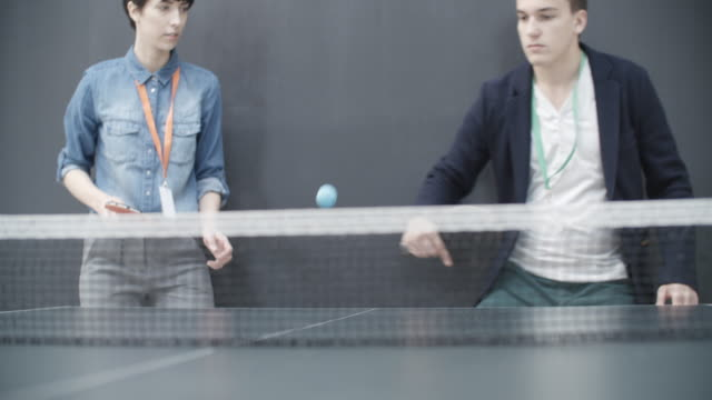 4k: young business people playing table tennis in their office. - leisure activity stock videos & royalty-free footage