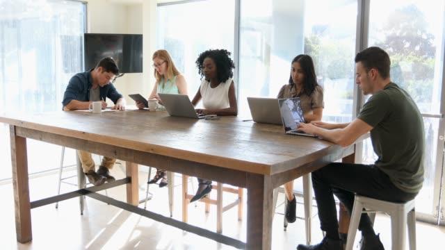 stockvideo's en b-roll-footage met jonge zakenlui werkt in een gedeelde office of cafe - nieuwe wegen betreden