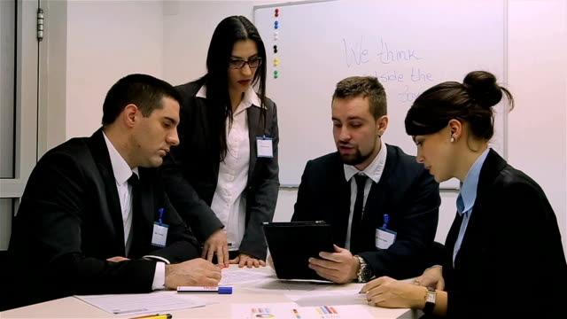 Junges Unternehmen Team Lesen von Daten auf digitalen Tablet auf dem Schreibtisch im Büro.