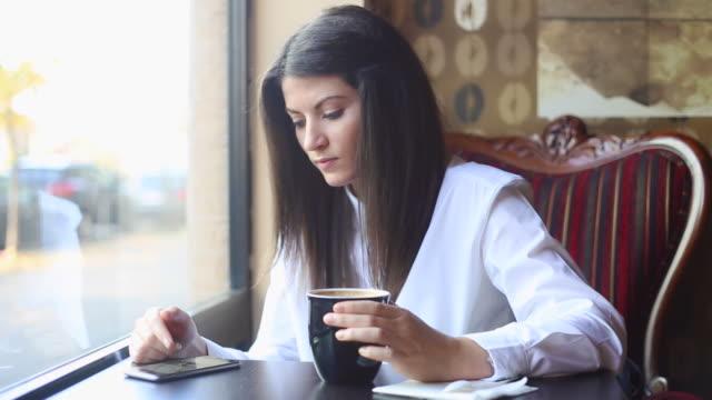 junge geschäftsfrau durchblättern ihrem smartphone im coffee shop. - nur junge frauen stock-videos und b-roll-filmmaterial