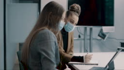 young business woman discussing business with her colleague working with face masks in the office during COVID-19 pandemic