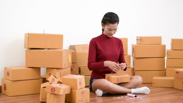 vídeos de stock, filmes e b-roll de mulher de negócios jovem fazendo pequenos negócios em casa - e commerce