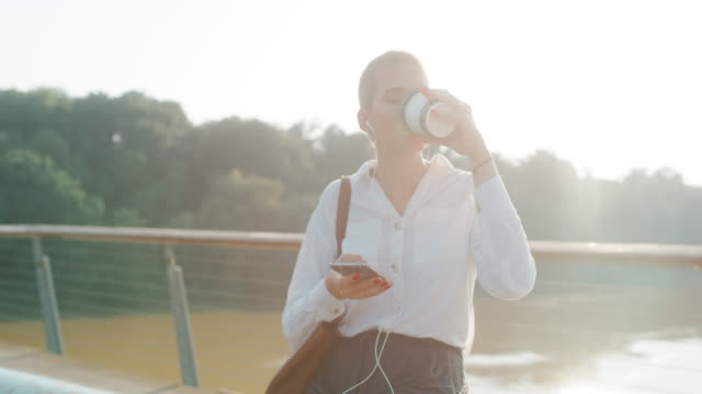 ms young business woman drinking coffee to go while using a smart phone - in ear headphones stock videos & royalty-free footage