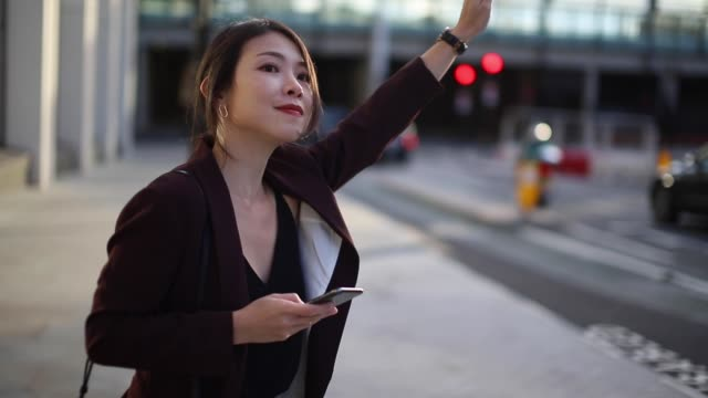 young business woman hailing a taxi during rush hour - businesswear stock videos & royalty-free footage