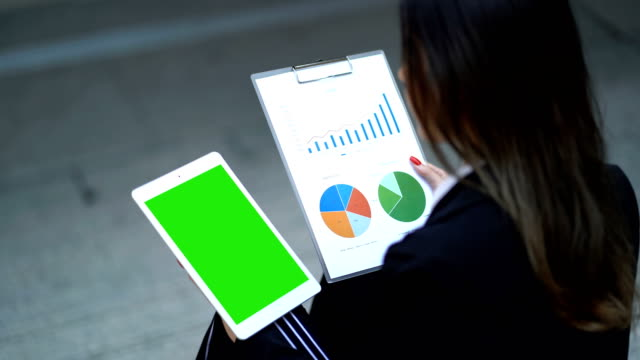 young business woman hold digital tablet in hand with greenscreen monitor checking analyze data of growing financial chart of sale, revenue and profit in the paper - keyable stock videos & royalty-free footage