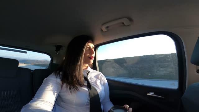 eine junge geschäftsfrau ist auf geschäftsreise, genießt einen schönen sonnigen tag auf dem weg, filmt sich mit einer gopro-kamera und redet. - photographing stock-videos und b-roll-filmmaterial