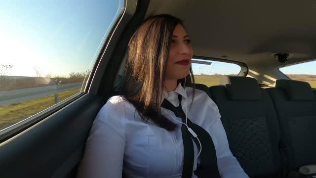vidéos et rushes de une jeune femme d'affaires est sur un voyage d'affaires, appréciant une belle journée ensoleillée le long du chemin, se filmant avec une caméra gopro et parlant. - mode of transport