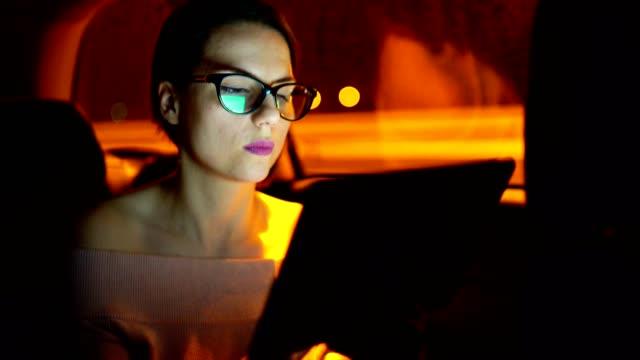 vídeos y material grabado en eventos de stock de la mujer joven de negocios está trabajando hasta tarde en la noche mientras ella está conduciendo en el asiento trasero del coche - mujer bella