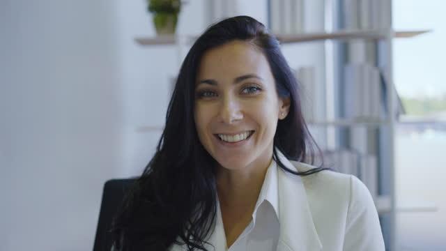 unga företag kvinna titta på webbkamera konferens ringer gör online. hon kan prata med en affärspartner eller ha en anställningsintervju på nätet. - framifrån bildbanksvideor och videomaterial från bakom kulisserna