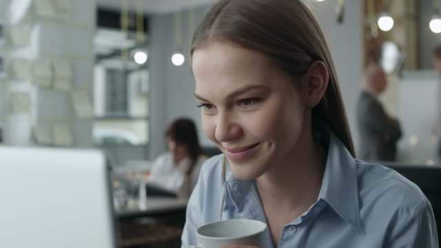 Young business woman looking at the laptop and drinking coffee