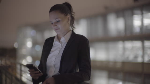 a young business woman on the phone at night - haar nach hinten stock-videos und b-roll-filmmaterial