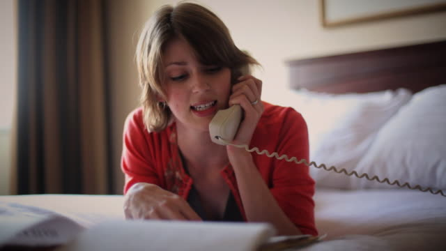 cu young business woman relaxing on bed while talking on phone and reviewing report in hotel room / madison, wisconsin, usa - landline phone stock videos & royalty-free footage