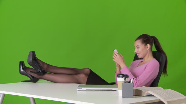 stockvideo's en b-roll-footage met young business woman relaxing with feet up on desk and texting on cell phone - achterover leunen