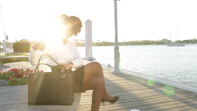 Young business woman sits on bench near water and takes coffee flask and lunch out of bag.