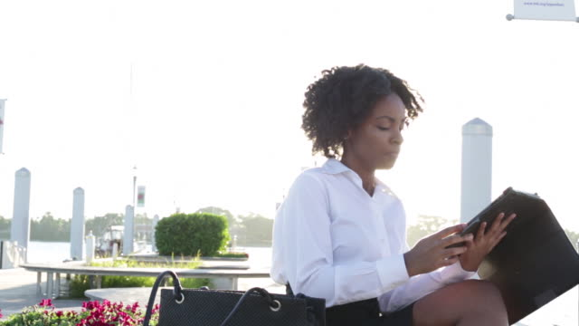 ms young business woman sitting outdoors on bench near water taking i pad out of handbag then drinking from coffee mug. - weibliche angestellte stock-videos und b-roll-filmmaterial