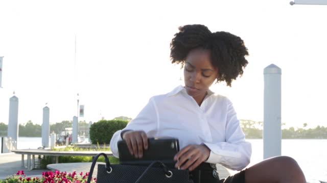 vídeos de stock, filmes e b-roll de ms young business woman sitting outdoors on bench near water taking i pad out of handbag. - bolsa tiracolo bolsa