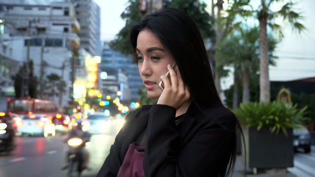 Young business woman talking with mobile phone with busy traffic as background.