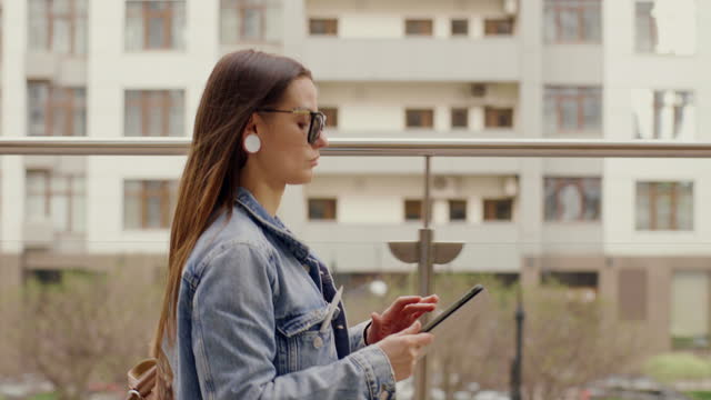 vidéos et rushes de young business woman uses tablet while walking in the city - 25 29 years