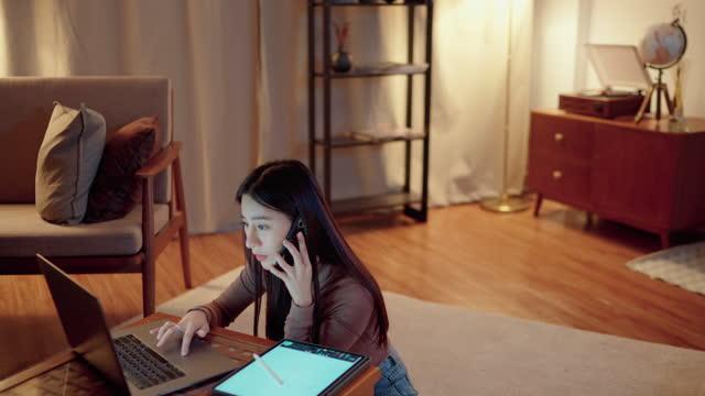 vídeos de stock, filmes e b-roll de jovem mulher de negócios usando um laptop e celular enquanto trabalhava na sala de estar à noite. - trabalhadora de colarinho branco