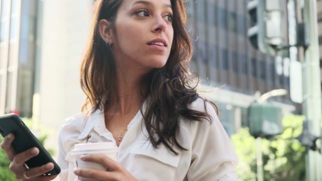 vídeos de stock, filmes e b-roll de mulher de negócio nova que usa o telefone esperto e o café bebendo em movimento - café bebida