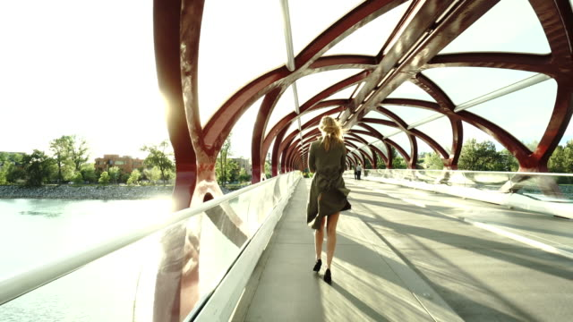 young business woman walks along river bridge - calgary stock videos & royalty-free footage