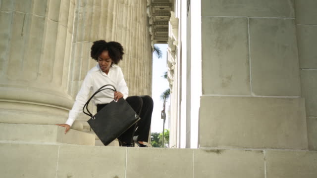 vídeos de stock, filmes e b-roll de young business woman walks into shot,sits on step and leans against pillar then gets ipad out of bag. - bolsa tiracolo bolsa
