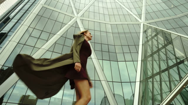 young business woman walks past architecture, through city center - grace stock videos & royalty-free footage