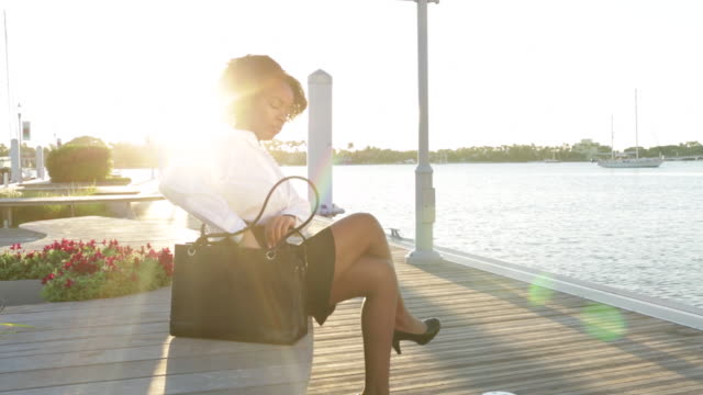 young business woman walks to bench near water, sits and enjoys a drink of coffee. - coffee drink stock videos & royalty-free footage