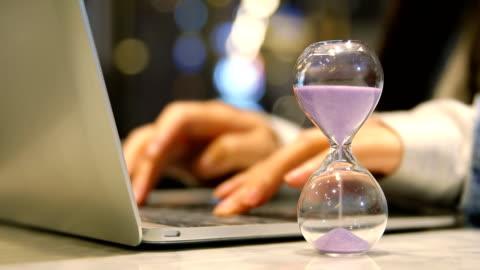 vidéos et rushes de femme jeune entreprise travaillant avec sablier - temps limité