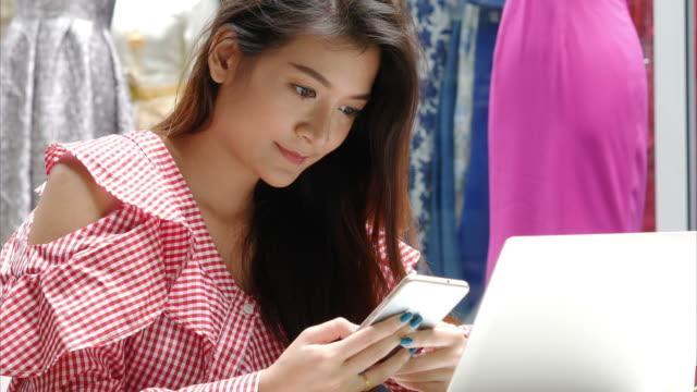 vidéos et rushes de femme d'affaires jeunes travaillant avec ordinateur portable et téléphone intelligent - payer