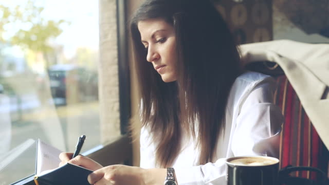 young business woman writing notes while drinking coffee. - report stock videos & royalty-free footage