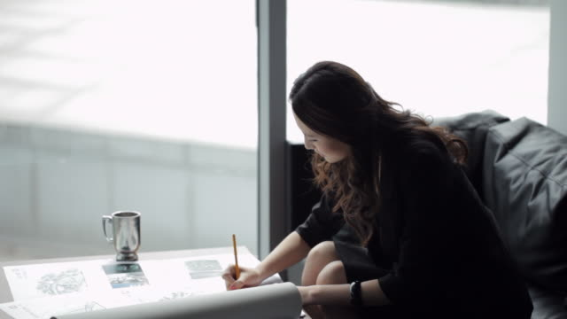 ms young business woman writing, sitting at coffee table by window/ beijing, china - coffee table stock videos & royalty-free footage