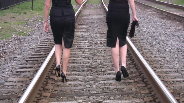 vidéos et rushes de jeune femme d'affaires marchant avec le haut hills. train path. - femme séductrice