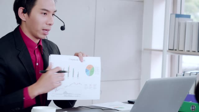 stockvideo's en b-roll-footage met young business working in an office chatting via an online laptop is described in graph paper holding about the company's business. - graph