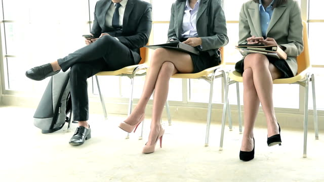 Young businessman and businesswomen using smartphones during waiting for job interview in corporate office