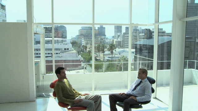 WS TD Young businessman and client having meeting in office, Cape Town, South Africa