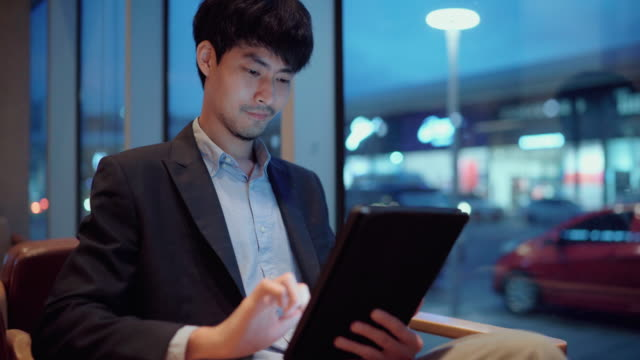 young businessman at a table in a cafe using digital tablet at night - three quarter length stock videos & royalty-free footage