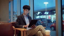 Young businessman at a table in a cafe using digital tablet at night