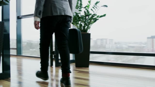 young businessman boy walking with briefcase in office, real time - arrival stock videos & royalty-free footage
