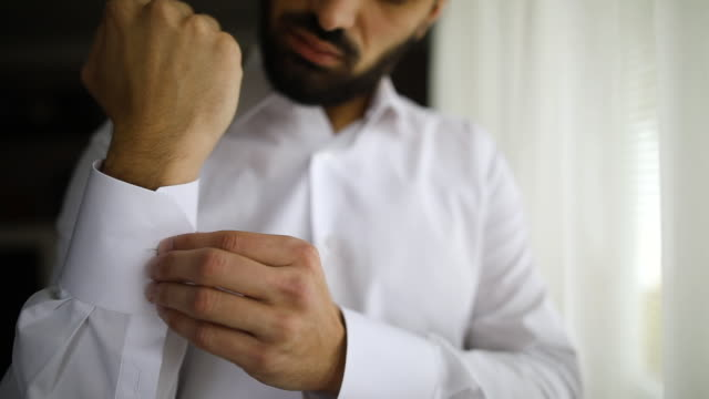 vídeos de stock e filmes b-roll de young businessman buttoning sleeve while standing near window in hotel room - vestuário de trabalho