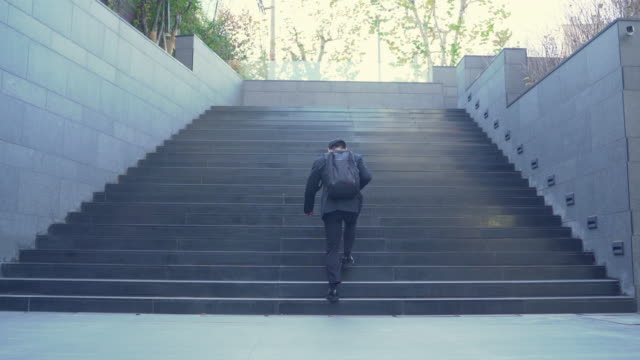 a young businessman carrying a bag and going up the stairs - zaino da montagna video stock e b–roll