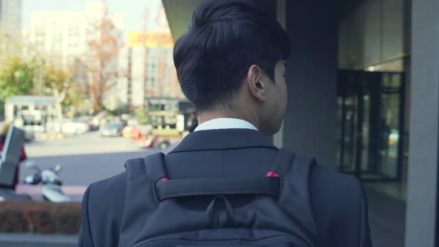 a young businessman carrying a bag over his shoulder on the way to work - shoulder bag stock videos & royalty-free footage
